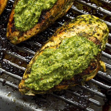 Grilled chimichurri chicken in a grilling pan, view from above. Flat lay, top view. Close-up.