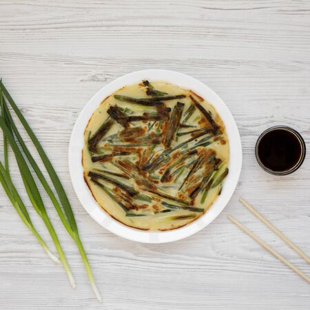 Homemade korean Pajeon scallion pancake on a white plate on a white wooden background, top view. Asian food. Flat lay, overhead, from above.