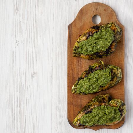 Grilled chimichurri chicken on a rustic wooden board on a white wooden table, top view. Flat lay, overhead, from above. Space for text.