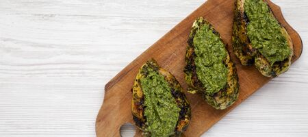 Grilled chimichurri chicken on a rustic wooden board on a white wooden background, top view. Space for text.