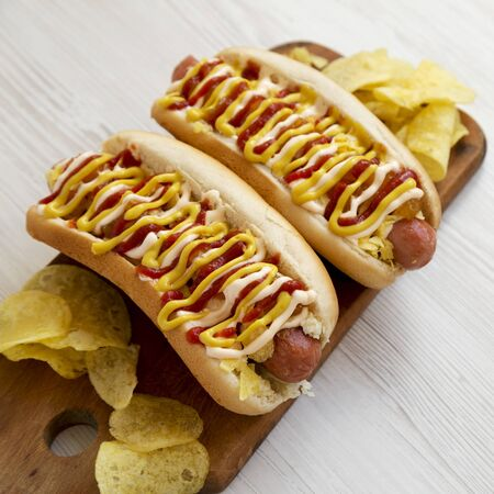 Homemade colombian hot dogs with pineapple sauce, chips, yellow mustard and mayo ketchup on a rustic wooden board on a white wooden surface, low angle view. Closeup.