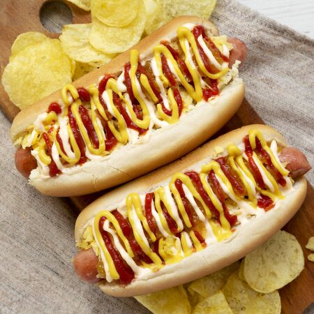 Delicious homemade colombian hot dogs with pineapple sauce, yellow mustard and mayo ketchup on a rustic wooden board, top view. Flat lay, from above, overhead. Closeup. Imagens