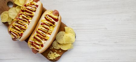 Homemade colombian hot dogs with pineapple sauce, yellow mustard and mayo ketchup on a rustic wooden board on a white wooden surface. Flat lay, from above, top view. Space for text.