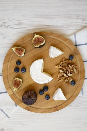 Camembert cheese with figs, blueberries and walnuts on a bamboo board over white wooden surface, top view. Food for wine. Close-up.