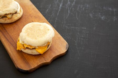 Homemade egg sandwich with cheese on a rustic wooden board on a black surface, side view. Copy space. 写真素材