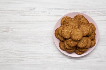 Cereal cookies on a pink plate on a white wooden background, top view. Flat lay, overhead, from above. Copy space.