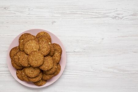Cereal cookies on a pink plate on a white wooden background, overhead view. Flat lay, top view, from above. Copy space.