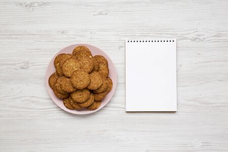 Cereal cookies on a pink plate, blank notepad on a white wooden surface, overhead view. Flat lay, top view, from above.