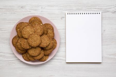 Cereal cookies on a pink plate, blank notebook on a white wooden background, overhead view. Flat lay, top view, from above. Copy space.