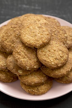 Cereal cookies on a pink plate on a black surface, side view. Close-up.