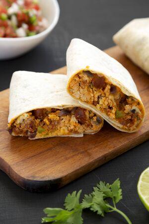 Homemade chorizo breakfast burritos on a black surface, side view. Closeup.