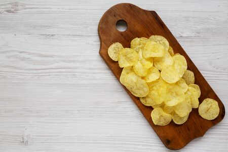 Yellow potato chips with salt on a wooden board on a white wooden background, top view. Flat lay, overhead, from above. Copy space. Stock Photo