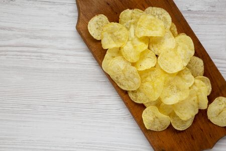 Yellow potato chips with salt on a wooden board on a white wooden surface, top view. Flat lay, overhead, from above. Space for text.