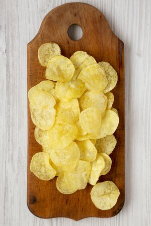 Yellow potato chips with salt on a wooden board on a white wooden background, top view. Flat lay, overhead, from above.