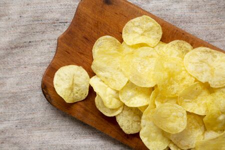 Delicious potato chips with salt on a rustic wooden board, top view. Flat lay, overhead, from above. Close-up. Stock Photo