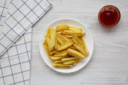 Homemade french fries with sour-sweet sauce on a white plate on a white wooden surface, top view. Flat lay, overhead, from above.