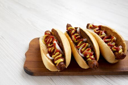 Homemade hot dogs with chicken sausage, ketchup and mustard on a rustic wooden board on a white wooden table, side view. Copy space.