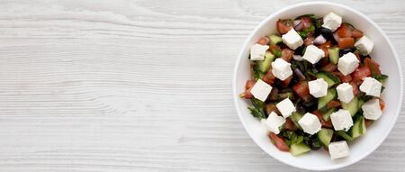 Homemade Shepards salad with cucumbers, feta and parsley in a white bowl on a white wooden background, overhead view. From above, overhead. Copy space.