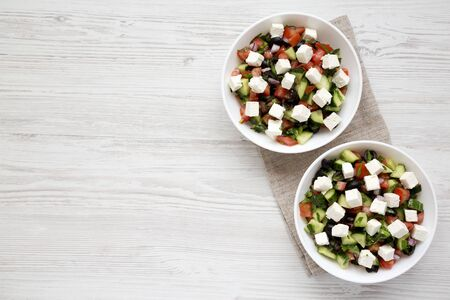 Homemade Shepards salad with cucumbers, feta and parsley in white bowls on a white wooden background, top view. From above, overhead, flat lay. Copy space.