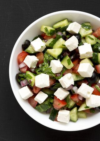 Homemade Shepherds salad with cucumbers, feta and parsley in a white bowl on a black surface, top view. From above, overhead, flat lay. Close-up. 版權商用圖片