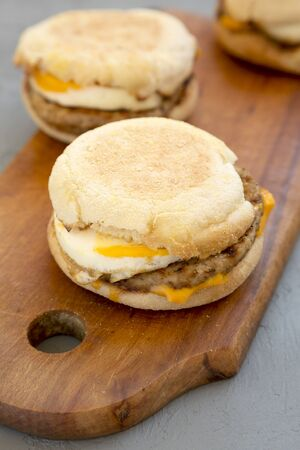 Homemade pork roll egg sandwich on a rustic wooden board on a concrete background, side view. Close-up. Stockfoto