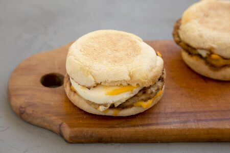 Homemade pork roll egg sandwich on a rustic wooden board on a concrete background, low angle view. Close-up.
