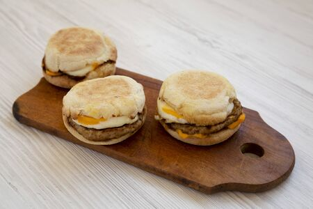 Homemade pork roll egg sandwich on a rustic wooden board on a white wooden background, low angle view. Closeup. Stockfoto
