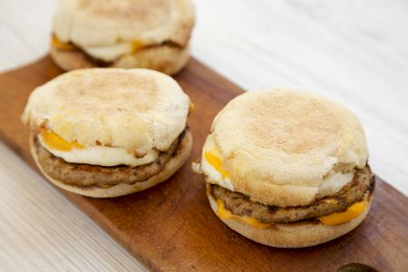 Homemade pork roll egg sandwich on a rustic wooden board on a white wooden table, low angle view. Close-up. Stockfoto