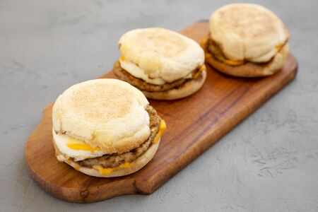 Homemade pork roll egg sandwich on a rustic wooden board on a gray background, low angle view. Closeup.
