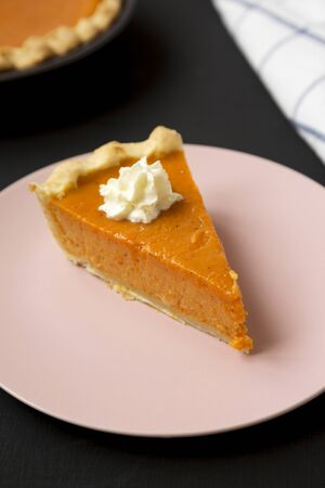 Homemade Thanksgiving pumpkin pie on a pink plate on a black background, low angle view. Close-up.