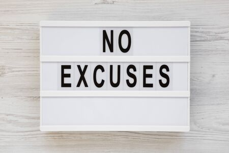 'No excuses' words on a modern board on a white wooden surface, top view. Overhead, from above, flat lay. Stockfoto