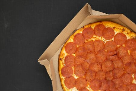 Tasty Pepperoni pizza in a box on a black background, top view. Overhead, from above, flat lay. Copy space.