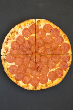 Delicious Pepperoni pizza over black background, top view. Overhead, from above, flat lay. Closeup. 版權商用圖片
