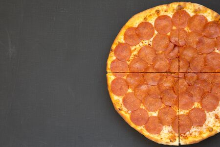 Tasty Pepperoni pizza over black background, top view. Overhead, from above, flat lay. Copy space.