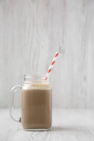 Glass jar mug filled with coffee, oat and banana smoothie on a white wooden surface, side view. Copy space. Stock fotó
