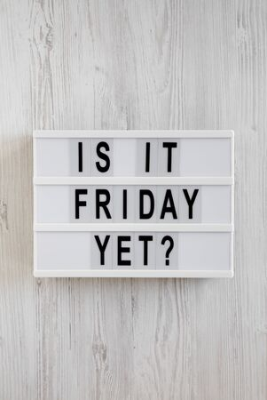 'Is it friday yet?' words on a modern board on a white wooden background, top view. Overhead, from above, flat lay. Close-up.
