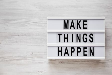 'Make things happen' words on a light box on a white wooden background, top view. Overhead, from above, flat lay. Copy space. Reklamní fotografie