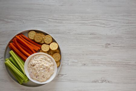 Homemade Pimento Cheese Dip with carrots, celery and crackers over white wooden surface, top view. Flat lay, overhead, from above. Copy space.