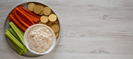 Homemade Pimento Cheese Dip with carrots, celery and crackers over white wooden background, top view. Flat lay, overhead, from above. Copy space.
