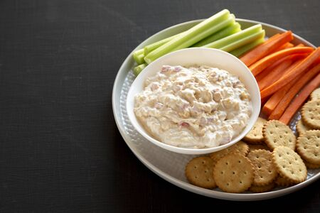 Homemade Southern Pimento Cheese Dip with carrots, celery and crackers, side view. Copy space.