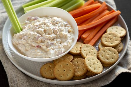 Homemade Southern Pimento Cheese with carrots, celery and crackers, low angle view. Close-up.