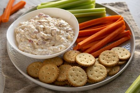 Homemade Pimento Cheese Dip with carrots, celery and crackers, low angle view. Close-up. Zdjęcie Seryjne