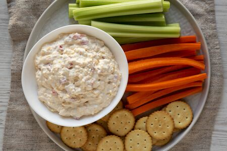 Homemade Pimento Cheese Dip with carrots, celery and crackers, top view. Flat lay, overhead, from above. Close-up.