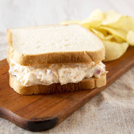 Tasty Homemade Pimento Cheese Sandwich with chips on a rustic wooden board, side view. Close-up.