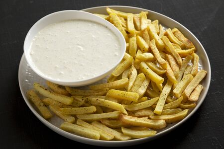 Homemade Crispy Ranch Fries on black surface, side view. Close-up.