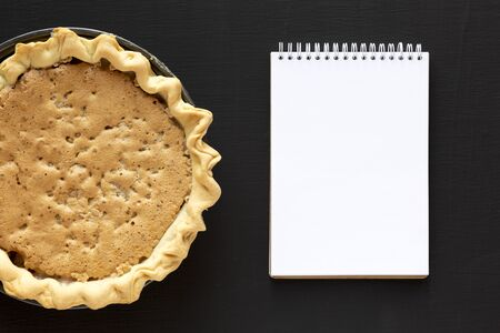Homemade Chocolate Walnut Derby Pie, blank notepad on a black background, top view. From above, overhead, flat lay.