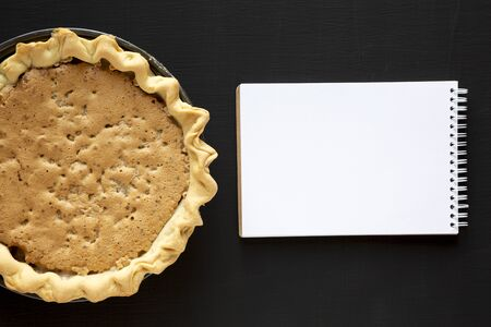 Homemade Chocolate Walnut Derby Pie, blank notebook on a black surface, top view. From above, overhead, flat lay.
