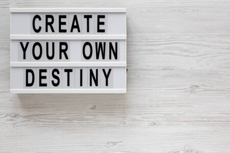'Create your own destiny' words on a modern board on a white wooden background, top view. Overhead, from above, flat lay. Space for text.