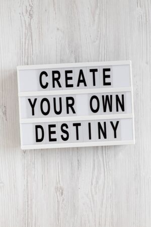 'Create your own destiny' words on a lightbox on a white wooden background, top view. Overhead, from above, flat lay. Close-up. Banque d'images
