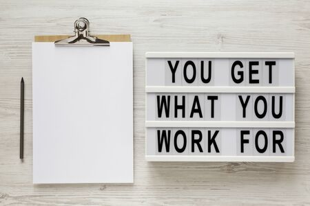 'You get what you work for' words on a lightbox, clipboard with blank sheet of paper on a white wooden background, overhead view. Top view, from above, flat lay.